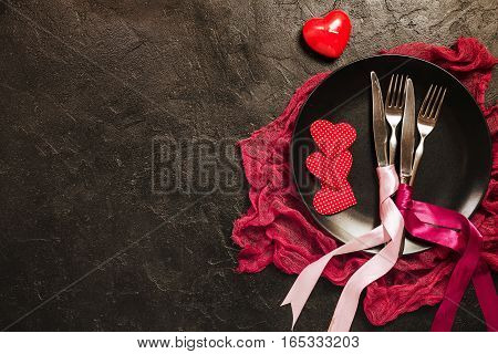 Valentine's day table setting. Table set with plate, knife and fork on black background. Top view and copy space. Love concept.