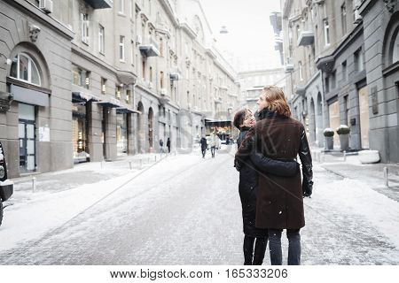 Couple has fun and laughs. kiss. Young hipster couple hugging each other in winter city.Winter love story a beautiful stylish young couple. Winter fashion concept with boyfriend and girlfriend