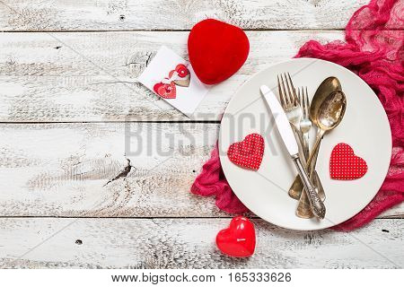 Valentine's day table setting. Table set with plate, knife, spoon and fork on white wooden background. Top view and copy space. Love concept.