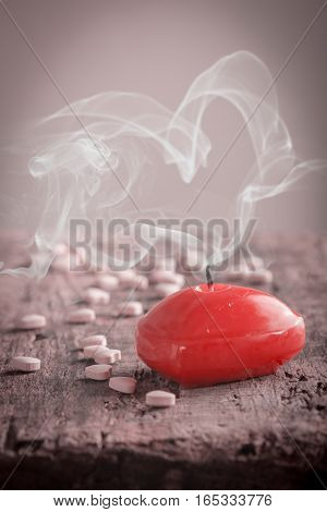 Red heart shaped candle and pink candies on wooden background, valentine's day concept