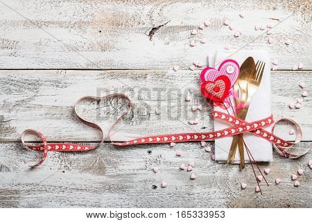 Valentines day table setting with napkin, knife, fork, red ribbon and hearts on white wooden background