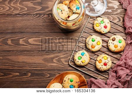 Homemade Candy Coated Chocolate Chip Cookies on wooden background, top view with copy space