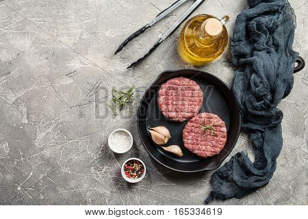 raw burgers - cutlets from organic beef meat with garlic and rosemary in a frying pan on gray background, top view with copy space