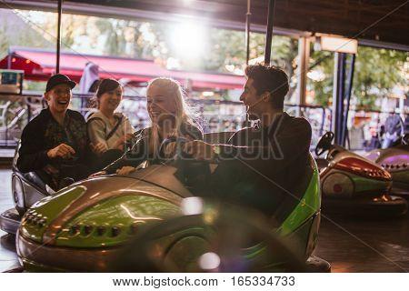 Friends Having Fun On Bumper Cars In Amusement Park