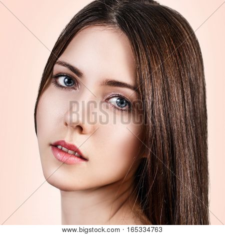 Young beautiful woman with healty fresh skin looking around over beige background. Spa concept.