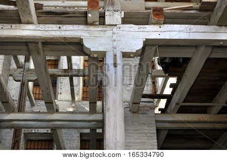 The frame of old industrial building. The wooden columns and beams in the interior.