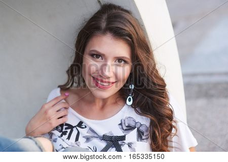 smiling young woman in a shirt with make-up near the wall.
