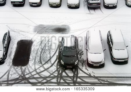 Ground parking cars after snowfall view from above. Automobiles covered with snow the traces of wheels and legs.