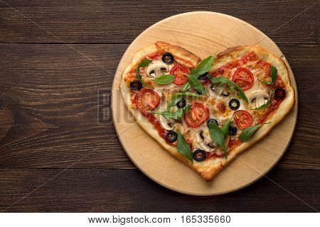 Heart Shaped Pizza On Cutting Board On Wooden Table.