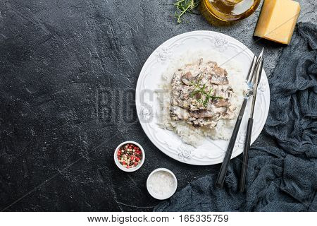 rice with mushrooms in a cream sauce on black background, top view with copy space