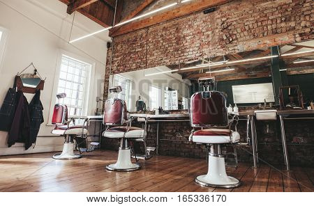 Horizontal shot of empty chairs in retro styled barbershop. Hair salon interior.