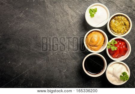bowls of various dip sauces on black background, top view with copy space
