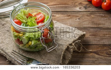 Served table with vegetable salad, fork, cherry tomatoes