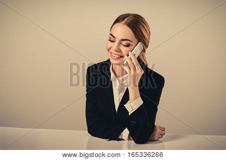 attractive dark-haired woman dressed in a black suit is sitting at a table in an office. Secretary talking on the phone