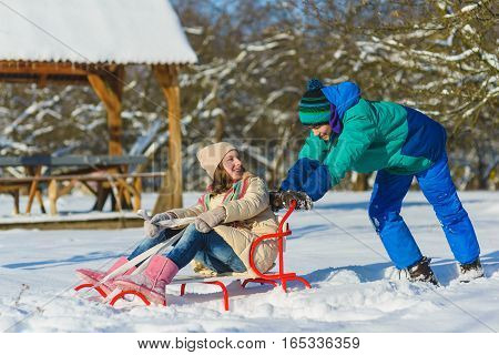 Happy boy and girl sledding in winter outdoor.