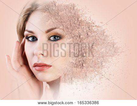 Woman face made from crumbly powder over beige background