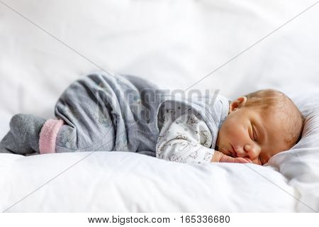 Cute adorable newborn baby sleeping in white bed. New born child, little girl six days old laying in bed. Family, new life, childhood, beginning concept.