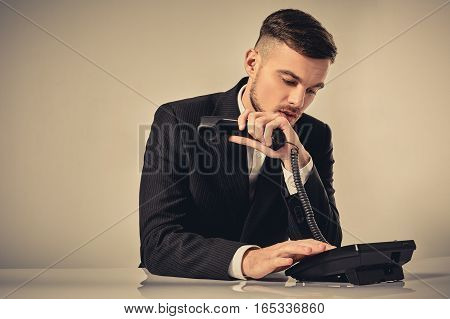 A young man dressed in a black suit dials the phone number while sitting in the office