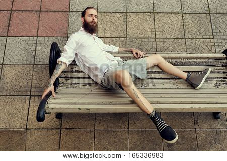 Cool Looking Guy With Tatoos And Long Beard Sitting On Chair Posing At Camera