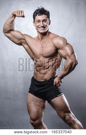 Beautiful Fitness Male Model Posing In Studio On White Grey Background.