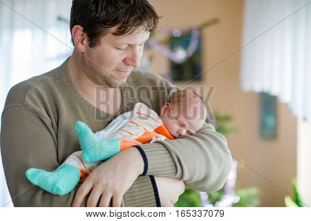 Happy proud young father holding his sleeping newborn baby daughter on arms. Dad with baby girl, love. New born child sleeping in dad arms. Bonding, family, new life