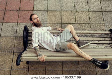 Bearded Tattooed Lying On Chair And Posing In Fashion Style