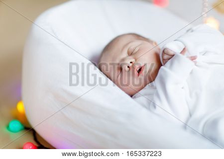 Cute adorable newborn baby sleeping in white bed. New born child, little girl laying in bed. Family, new life, childhood, beginning concept.