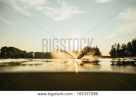 Low angle shot of man water skiing at sunset . Man wakeboarding on a lake.