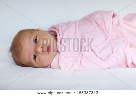 One week old adorable newborn baby wrapped in pink blanket and hairband looking at the camera. Closeup of cute peaceful child, little baby girl sleeping. Family, Birth, new life