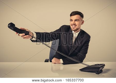 Portrait of attractive businessman holding telephone in his hand. This call is for you concept. A young man in a black suit dials the phone number while sitting in the office