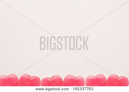 Pink Valentine's day heart shape lollipop candies on empty white paper background. Love Concept. Minimalism colorful hipster style.