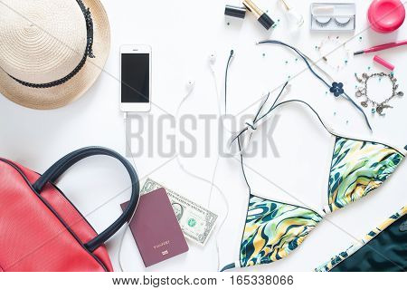 Flat lay set of girl essentials with blue bikini mobile phone passport and accessories for summer vacation on white background