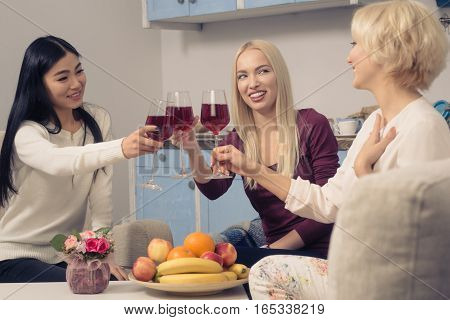 Toned picture of happy friends girls drinking red wine and smiling while spending free time at home. Beautiful cheerful ladies having party in kitchen after hard working day.