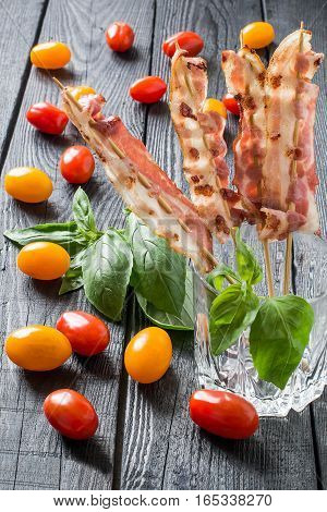 Grilled bacon on skewers in a glass, red and yellow cherry tomatoes and basil on a dark wooden table