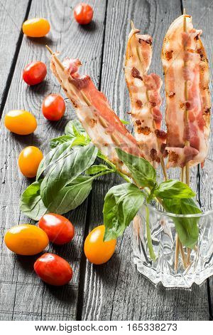 Grilled bacon on skewers in a glass red and yellow cherry tomatoes and basil on a dark wooden table