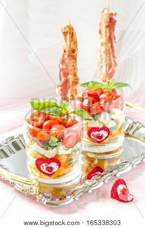 Festive verrines with grilled bacon on skewers. Original feed caprese salad in a glass. Serving for the holidays: Valentine's Day birthday Mother's Day. Selective focus vertical
