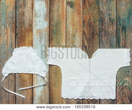 coif and shirt for a newborn on an old rustic wooden table closeup top view. with space for your text