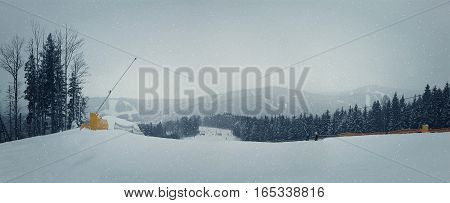 Snowing winter day on the ski slope. Perfect destination for a winter vacation in the peaks fir forests and ski slopes all covered by snow.
