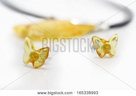stud earrings from natural baltic amber on white acrylic surface on background of amber beads