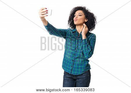 Young woman in blue shirt makes selfie on a white background. isolated