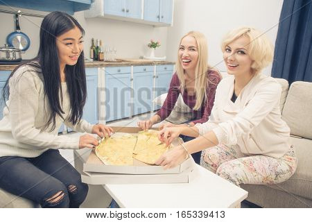Toned picture of happy best friends girls eating pizza with four cheeses while having party in kitchen at home. Beautiful ladies looking at camera and smiling.