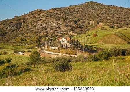 Cyprus landscape with mountains and village house.
