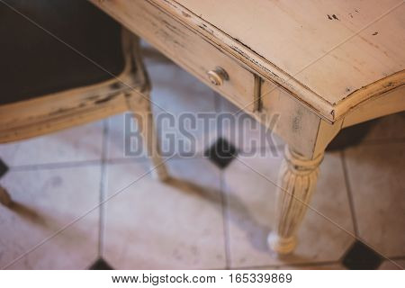 Old white table. Wooden desk with drawer. Vintage furniture store.