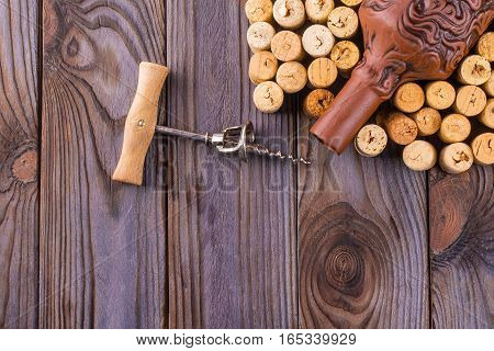 bottle of wine with corks on wooden table background.