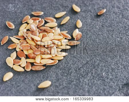 Golden and brown flax seed on gray slate background with copy space