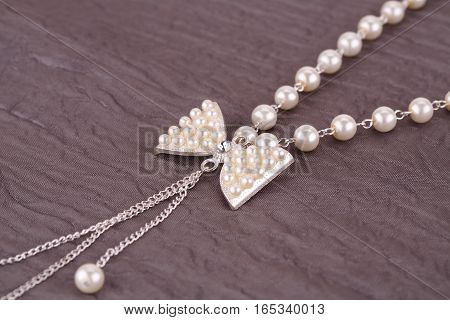 Silver necklace with pearls on fabric background.