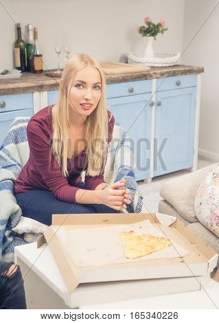 Toned picture of sad blond lady resting and relaxing after having party with pizza at home. Pretty woman sitting in arm chair and looking at camera.