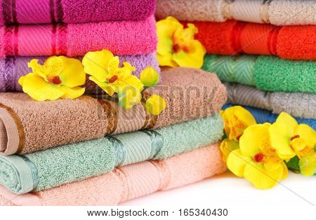 Colorful towels stacks with flowers closeup picture.