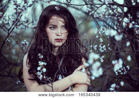 Fashion Art Mystical Spring Model Girl Portrait in Moonlight Night. Sexy Glamour Summer Beautiful Woman with Healthy and Beauty Brown Hair with flowers over nature blurred background. Fairy