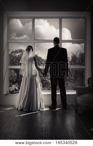 Silhouette of the groom and bride in the room against the background of a window